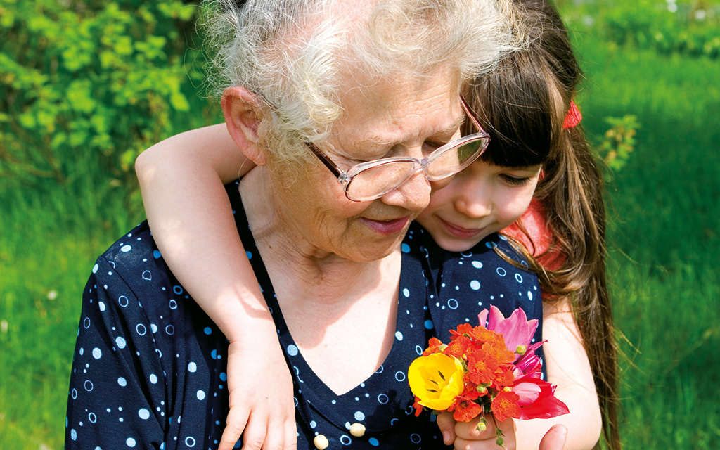 Photo d'une personne agée et d'une fillette tenant un bouquet de fleurs